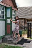 Young rustic teacher woman in retro dress with old-fashioned suitcase opens the door of a rural school holding the door handle. Teacher woman in retro dress with stock photography
