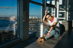 Young 90s fashion woman sitting near the huge window. Young 90s fashion woman sitting on window background with sunlight on face Stock Photography