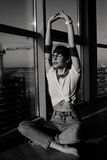 Young 90s fashion woman sitting near the huge window. Young 90s fashion woman sitting on window background with sunlight on face. Black and white shot Stock Images