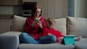 Young 30s mother in glasses using mobile phone with little girl using tablet computer sitting on couch at home. Family