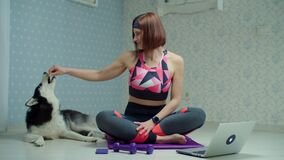 Young 30s woman in sportswear making yoga and meditation exercises on fitness mat with Siberian Husky dog nearby at home
