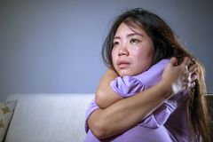 Free Young Sad And Depressed Asian Japanese Woman At Home Sofa Couch Crying Desperate And Helpless Suffering Anxiety And Depression Fee Stock Photo - 124909880