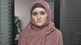 Young sad Arab girl in pink hijab crying, mourns, upset. Grief concept Looks at the camera, portrait. 60 fps. Young sad Arab girl in pink hijab crying, mourns stock video footage