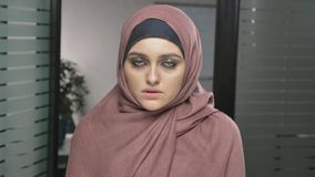 Young sad Arab girl in pink hijab, mourns, upset. Grief concept Looks at the camera, portrait. 60 fps. 4k stock video