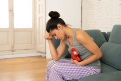 Young sad attractive woman having painful stomachache from period pain and menstrual cramps. Young beautiful latin hispanic woman in painful expression suffering stock photo