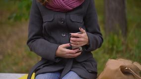 Young beautiful upset woman puts mobile phone in the her bag, sitting on bench in autumn park. Woman using her. Young sad beautiful woman sitting on bench in the stock footage