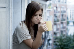 Young sad beautiful woman suffering depression looking worried and wasted on home balcony Stock Photography
