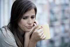 Young sad beautiful woman suffering depression looking worried and wasted on home balcony Royalty Free Stock Photo