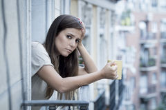 Young sad beautiful woman suffering depression looking worried and wasted on home balcony. With an urban view drinking tea cup in lonely depressed and desperate Royalty Free Stock Images