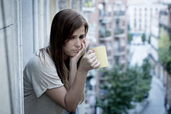 Young sad beautiful woman suffering depression looking worried and wasted on home balcony. With an urban view drinking tea cup in lonely depressed and desperate Stock Image