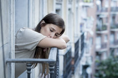 Young sad beautiful woman suffering depression looking worried and wasted on home balcony Stock Photo