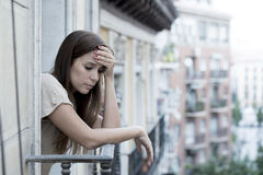 Young sad beautiful woman suffering depression looking worried and wasted on home balcony. With an urban view in lonely depressed and desperate female concept Royalty Free Stock Photography