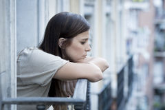 Young sad beautiful woman suffering depression looking worried and wasted on home balcony. With an urban view in lonely depressed and desperate female concept Stock Images