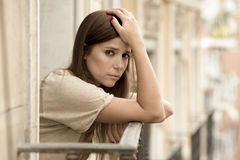 Young sad beautiful woman suffering depression looking worried and wasted on home balcony. With an urban view in lonely depressed and desperate female concept Stock Photos
