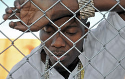 Young sad black man behind a fence. Attractive African American young man revealing his sadness and depression while leaning against a chain link fence Royalty Free Stock Photography