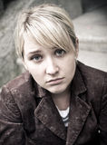 Young sad blonde girl with fringe. Close-up of young sad blonde girl with fringe, dressed in velvet brown jacket Stock Image