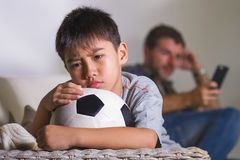 Young sad and bored child at home couch feeling frustrated and unattended waiting his father for playing football while man stock image