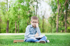 Young sad boy with a books and laptop Royalty Free Stock Images
