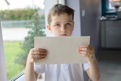 Young sad boy in a polo shirt, holding an empty copyspace sheet of paper Stock Images