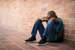 Young sad boy at school. Young boy sitting alone with sad feeling at school. Depressed african child abandoned in a corridor and leaning against brick wall Stock Photo