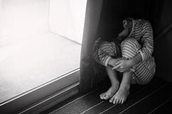 Young sad boy sitting on the floor Stock Image
