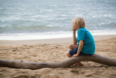 Young sad boy thinking on the beach. Portrait of a young sad boy sitting on a log on the beach thinking with copy-space royalty free stock photo