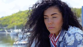 Beautiful sad brunette. Young sad brunette stands at the embankment and thinks about something personal. Upset woman looks at the distance and in camera stock video footage