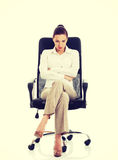 Young sad business woman sitting on a chair. Royalty Free Stock Images