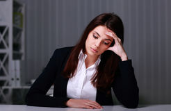 Young sad businesswoman sitting at the table on her workplace royalty free stock photo