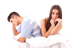 A young sad couple in bed having problems and cris. Portrait of a young couple having problems in bed stock photo