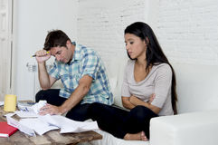 Young sad couple at home living room couch calculating monthly expenses worried in stress Stock Images