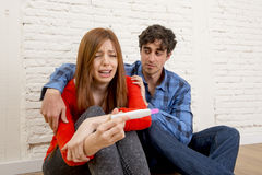 Young sad couple scared with pregnant girl reading pink positive pregnancy test crying overwhelmed Royalty Free Stock Photos