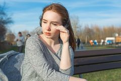 Young, sad cry redhead girl in the spring in the park near the river listens to music through wireless bluetooth headphones stock photo