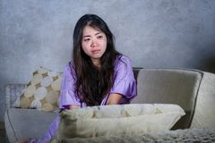 Young sad and depressed Asian Chinese woman crying alone desperate sitting at home sofa ouch worried in pain and stress suffering. Depression and anxiety royalty free stock images