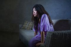 Young sad and depressed Asian Chinese woman crying alone desperate sitting at home sofa ouch worried in pain and stress suffering. Depression and anxiety stock photography