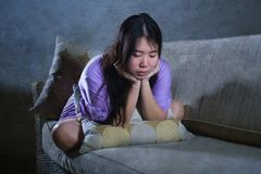 Young sad and depressed Asian Chinese woman crying alone desperate sitting at home sofa ouch worried in pain and stress suffering. Depression and anxiety royalty free stock photography