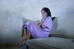 Young sad and depressed Asian Chinese woman crying alone desperate sitting at home sofa ouch worried in pain and stress suffering. Depression and anxiety stock photo