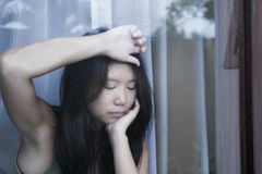Young sad and depressed Asian Chinese woman looking thoughtful through window glass suffering pain and depression in sadness conce Royalty Free Stock Photos