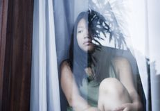Young sad and depressed Asian Chinese woman looking thoughtful through window glass suffering pain and depression in sadness conce. Young sad and depressed Asian Stock Image