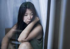 Young sad and depressed Asian Chinese woman looking thoughtful through window glass suffering pain and depression in sadness conce Stock Photo