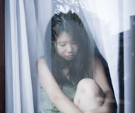 Young sad and depressed Asian Chinese woman looking thoughtful through window glass suffering pain and depression in sadness conce Royalty Free Stock Images