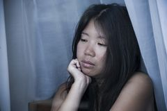 Young sad and depressed Asian Chinese woman looking thoughtful through window glass suffering pain and depression in sadness conce. Young sad and depressed Asian Royalty Free Stock Image