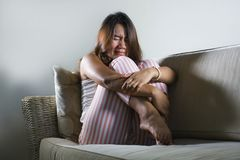 Young sad and depressed Asian Indonesian woman sitting at home couch crying frustrated and upset suffering stress and depression. Dramatic lifestyle portrait of stock photos