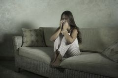Young sad and depressed Asian Indonesian woman sitting at home couch crying frustrated and upset suffering stress and depression. Dramatic lifestyle portrait of stock photo