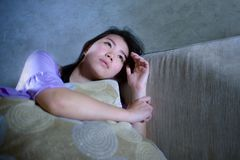 Young sad and depressed Asian Korean woman crying alone desperate and worried in pain sitting at home sofa couch suffering depress stock images