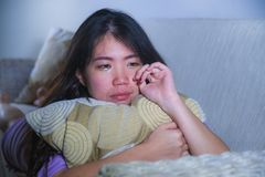 Young sad and depressed Asian Korean woman at home sofa couch crying desperate and helpless suffering anxiety and depression feeli. Ng pain in relationship and royalty free stock image