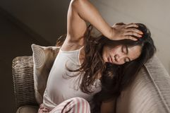 Young sad and depressed Asian woman in pajamas at home sitting at home couch crying frustrated and upset suffering stress and. Dramatic lifestyle portrait of royalty free stock images