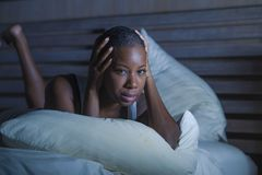 Young sad depressed black african American woman in bed sleepless feeling desperate worried suffering depression problem insomnia. Young sad and depressed black stock images