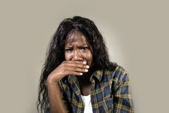 Young sad and depressed black African American woman crying anxious and overwhelmed feeling sick and stressed isolated on studio b. Ackground suffering royalty free stock image