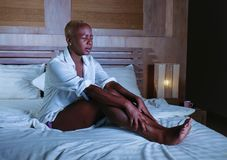 Young sad depressed black afro american woman in bed suffering depression feeling miserable and sick looking worried and desperate. Sleepless at night on her royalty free stock photo